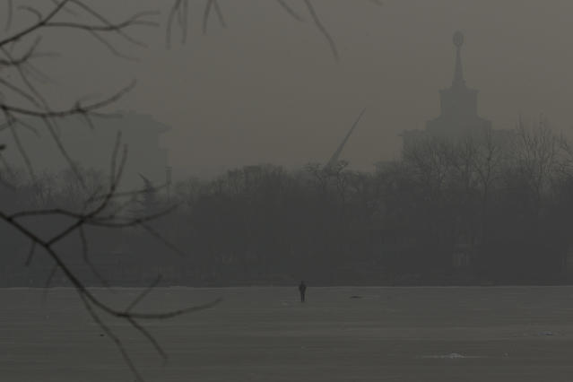 A man walks on an frozen lake on a hazy day in Beijing, China, Monday, Jan. 14, 2013. Beijing schools kept children indoors and hospitals saw a spike in respiratory cases Monday following a weekend of off-the charts pollution in China's smoggy capital, the worst since the government began being more open about air-quality data. (AP Photo/Alexander F. Yuan)