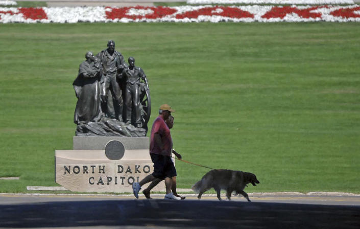 """FILE - In this Aug. 19, 2013 file photo, people walk a dog across Sixth Street in front of the state capitol in Bismarck, N.D. Lawmakers are trying to stop 144 cities across the U.S. from losing their designations as """"metropolitan areas"""" because the federal government is upgrading the standard from a minimum of 50,000 residents in its core to a minimum of 100,000 people. Bismark is among those at risk of losing the designation. (Tom Stromme/The Bismarck Tribune via AP, File)"""