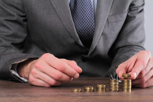 Businessman stacking coins on a table, in piles of increasing height.