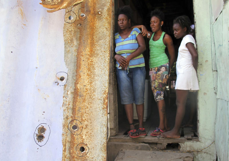 Bullet holes fill a sheet metal fence in front of the doorway of a home where the relatives of Nicketa Cameron, who was killed in crossfire, stand a few feet from where she died in the Denham Town ghetto in Kingston, Jamaica, Thursday March 8, 2012. Cameron, 13, was standing by a washing machine in a narrow hallway facing the street when she was killed by a bullet to the head during a roughly 40-minute gun battle between police and criminals. The family insists the bullets were fired through the sheet metal fence into their home by police. (AP Photo/David McFadden)