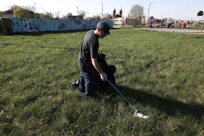 Mower Gang member Kevin Johnson, of Sterling Heights, clears debris from Duweke Park in Detroit, Wednesday May 1, 2013. The Mower Gang, a group of volunteer lawn mower riders, adopt parks beginning in the spring and keep them free of high-grass throughout the summer. (AP Photo/Paul Sancya)