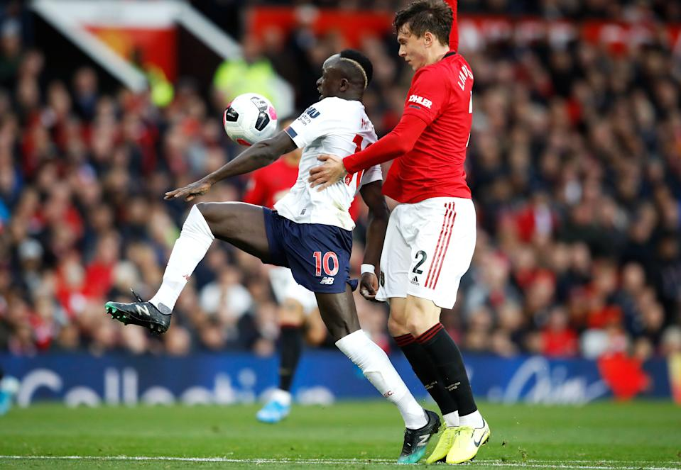Liverpool's Sadio Mane (left) gets pasts Manchester United's Victor Lindelof to score his side's first goal before the goal is ruled out by VAR for handball during the Premier League match at Old Trafford, Manchester. (Photo by Martin Rickett/PA Images via Getty Images)