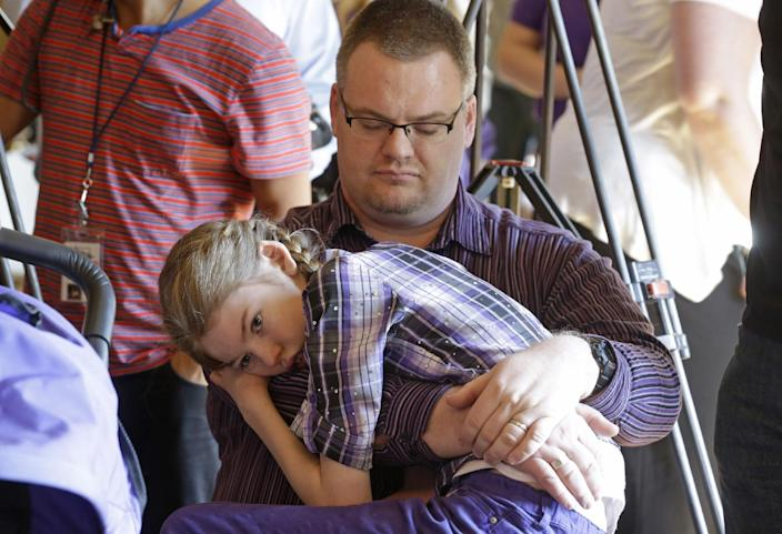 Marshall Christensen, of Provo, holds his daughter Jessica, 13, as they wait for the H.B 105 bill signing ceremony at the Utah State Capitol, Tuesday, March 25, 2014, in Salt Lake City. Parents of Utah children with severe epilepsy are cheering a new state law that allows them to obtain a marijuana extract they say helps with seizures, but procuring it involves navigating a thorny set of state and federal laws. Utah's Republican Gov. Gary Herbert has already approved the law and held the signing ceremony Tuesday afternoon. The new law doesn't allow medical marijuana production in Utah but allows families meeting certain restrictions to obtain the extract from other states. (AP Photo/Rick Bowmer)