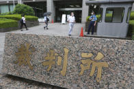 """People walk in the compound of the Tokyo District Court where a trial of two Americans suspected of helping former Nissan chairman Carlos Ghosn flee Japan, opens in Tokyo, Monday, June 14, 2021. The court is starting the trial of trial of Michael Taylor, a former Green Beret, and his son Peter Taylor in connection with the brash escape of Ghosn from Japan to Lebanon in late 2019. The Japanese plate reads: """"Court."""" (AP Photo/Koji Sasahara)"""