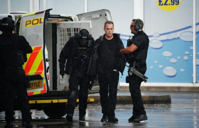 Armed police detain a man (centre) at the scene