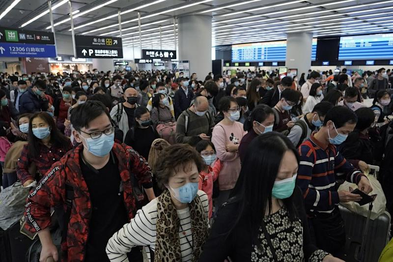Large amounts of people in Wuhan all wearing face masks.
