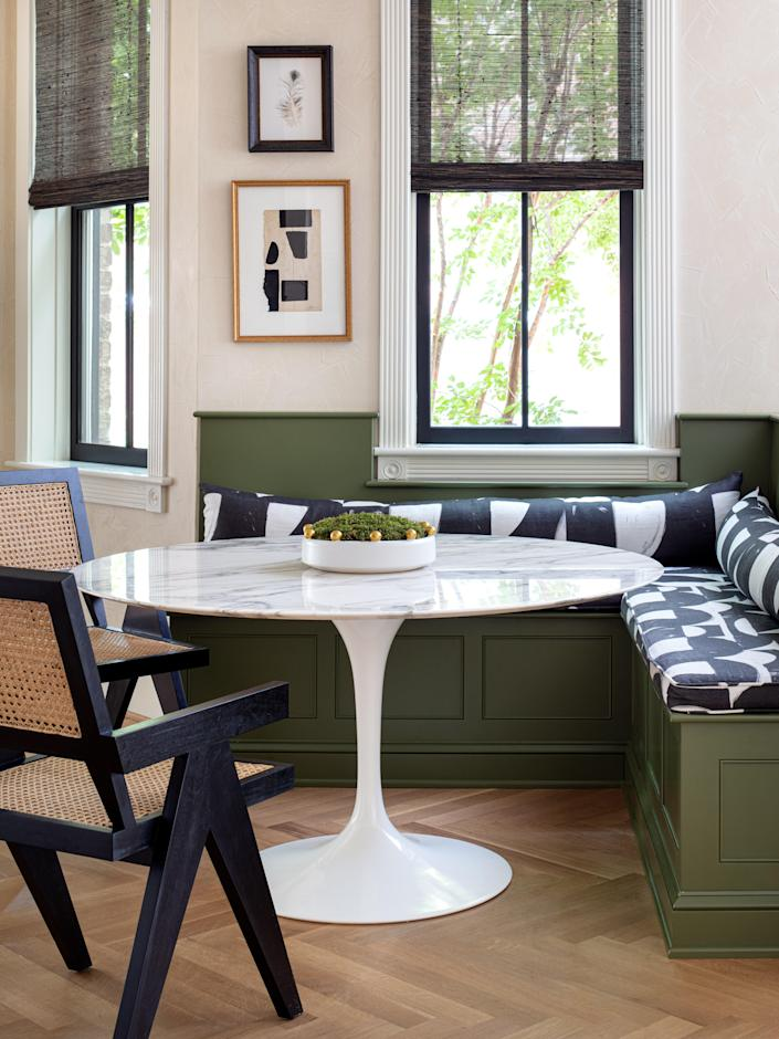 Green from the kitchen cabinets continues into the breakfast nook. The banquette is topped it with cushions upholstered in Lindsay's Onyx Belgian Linen. An Eero Saarinen tulip table is paired with Noir chairs; a framed peacock feather and artwork by Catherine Booker Jones hang on the wall.