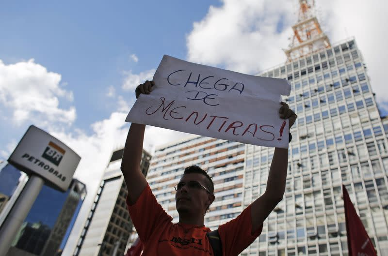 A member of Brazil's Movimento dos Sem-Teto holds up a sign in a protest in front of the Petrobras headquarters in Sao Paulo