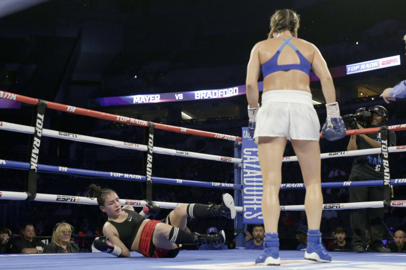 Mikaela Mayer looks at Vanessa Bradford after knocking her down during their super featherweight NABF title boxing bout in Omaha, Neb., Saturday, Oct. 13, 2018. Mikaela Mayer won by unanimous decision. (AP Photo/Nati Harnik)