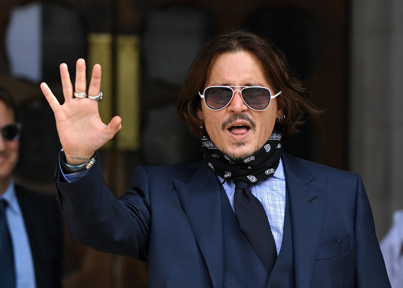 Johnny Depp waves to crowds on day 6 of his libel case against The Sun Newspaper at the Royal Courts of Justice, Strand on July 14, 2020 in London, England. American actor Johnny Depp is taking News Group Newspapers, publishers of The Sun, to court over allegations that he was violent towards his ex-wife, Amber Heard, 34