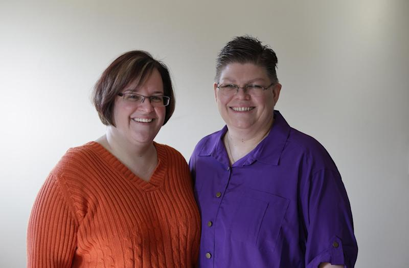 April DeBoer, left, and Jayne Rowse, and pose at their home in Hazel Park, Tuesday, March 5, 2013. The lesbian couple's desire to adopt each other's children has grown into a potentially ground-breaking challenge to Michigan's ban on same-sex marriage. The two Detroit-area nurses filed a lawsuit to try to overturn restrictions on adoption by same-sex partners. But at the judge's invitation, the case has taken an extraordinary turn and now will test the legality of a 2004 constitutional amendment that says only marriage of a man and woman is recognized in Michigan. (AP Photo/Paul Sancya)