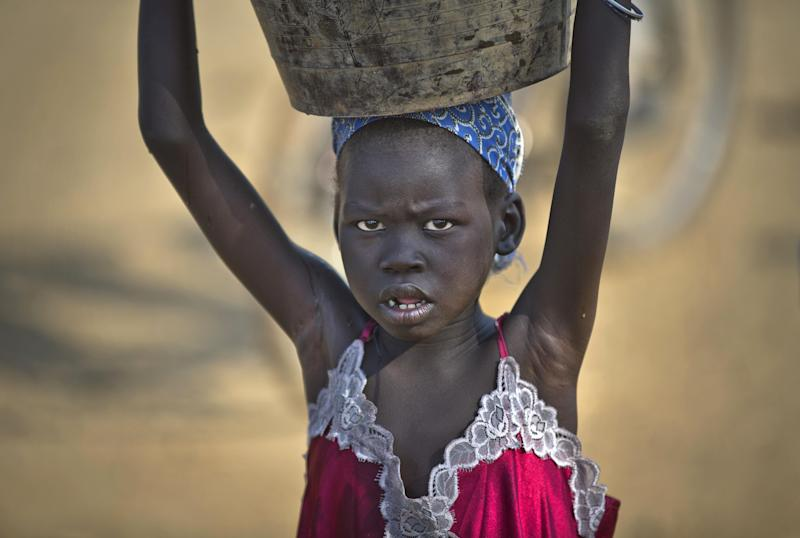 A young displaced girl carries a bucket of water back to her makeshift shelter at a United Nations compound which has become home to thousands of people displaced by the recent fighting, in the Jebel area on the outskirts of Juba, South Sudan Tuesday, Dec. 31, 2013. Anti-government rebels took control of nearly all of the strategic city of Bor on Tuesday even as officials announced that representatives from the government and the rebels had agreed to hold talks for the first time. (AP Photo/Ben Curtis)