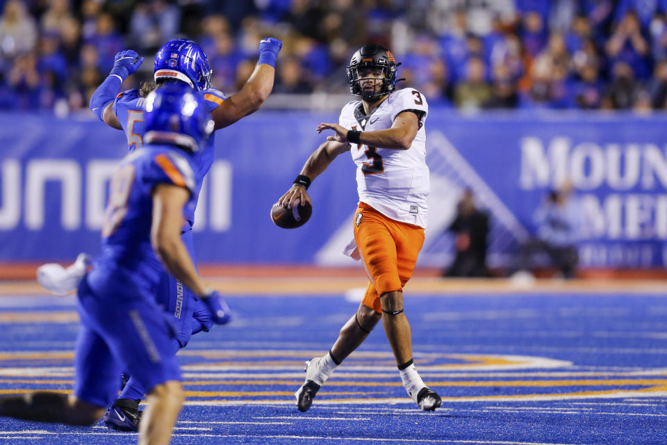 Oklahoma State quarterback Spencer Sanders (3) looks for a receiver as he is pressured by the Boise State defense during the second half of an NCAA college football game Saturday, Sept. 18, 2021, in Boise, Idaho. (AP Photo/Steve Conner)