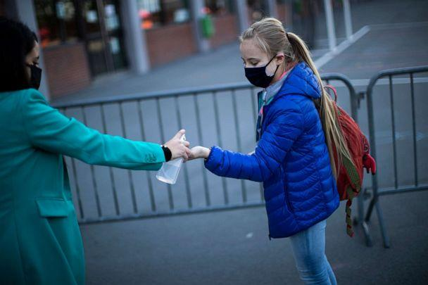 PHOTO: A student wearing a face mask is offered hand gel before entering the classroom at Les Magnolias primary school during the partial lifting of coronavirus, COVID-19, lockdown regulations in Brussels, May 18, 2020. (Francisco Seco/AP)