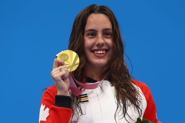Aurélie Rivard  of Canada poses on the podium with her gold medal in the women's 100-metre freestyle. (Marko Djurica/Reuters - image credit)