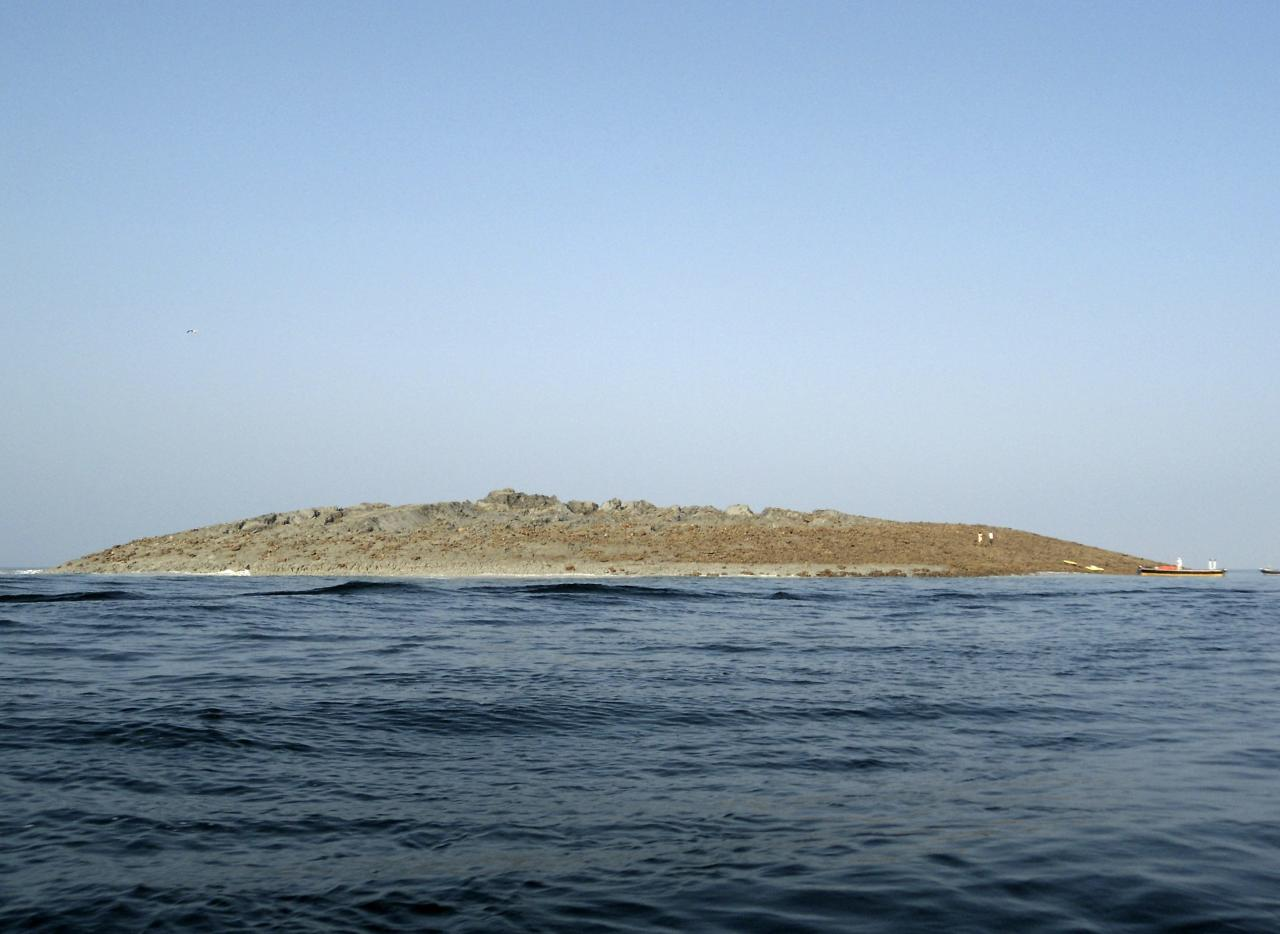 An island that rose from the sea following an earthquake is pictured off Pakistan's Gwadar coastline in the Arabian Sea September 25, 2013. A major earthquake hit a remote part of western Pakistan on Tuesday, killing at least 45 people and prompting the new island to rise from the sea just off the country's southern coast. The earthquake was so powerful that it caused the seabed to rise and create a small, mountain-like island about 600 meters off Pakistan's Gwadar coastline. Television channels showed images of a stretch of rocky terrain rising above the sea level, with a crowd of bewildered people gathering on the shore to witness the rare phenomenon. REUTERS/Stringer (PAKISTAN - Tags: ENVIRONMENT DISASTER)