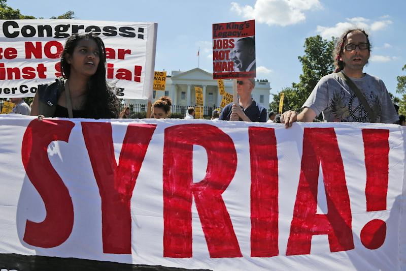 Anti-war demonstrators protest against possible U.S. military action in Syria in front of the White House in Washington, Saturday, Sept. 7, 2013. (AP Photo/Charles Dharapak)