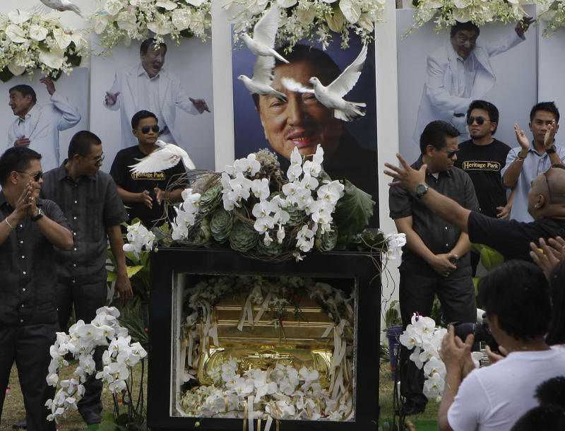 """Doves fly over the tomb of the country's """"King of Comedy"""", Rodolfo Vera Quizon Sr., locally known as """"Dolphy"""", during funeral rites at a cemetery in Taguig, south of Manila, Philippines on Sunday July 15, 2012. Quizon starred in more than 200 films in his 66-year career. The 83-year-old died Tuesday of multiple organ failure, kidney ailments and complications from pneumonia.(AP Photo/Aaron Favila)"""