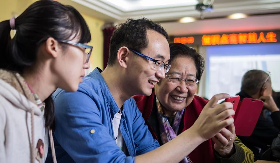 A representative of Beijing-based NGO See Young (centre) shows an elderly client how to use digital devices and mobile phone apps. Photo: courtesy of See Young