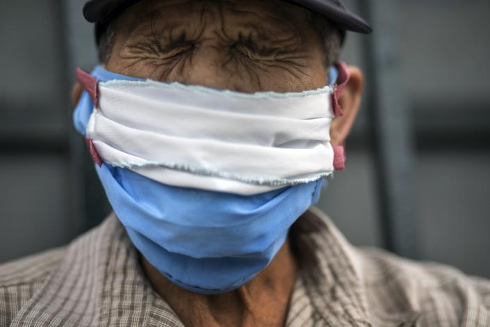 Julio Morales, 72, wearing a self-made face mask amid the spread of the new coronavirus, winces from arthritic pain as he waits to sign up for a place to sleep outside the Plaza de Toros de Acho bullfighting ring in Lima, Peru, Tuesday, March 31, 2020. (AP Photo/Rodrigo Abd)