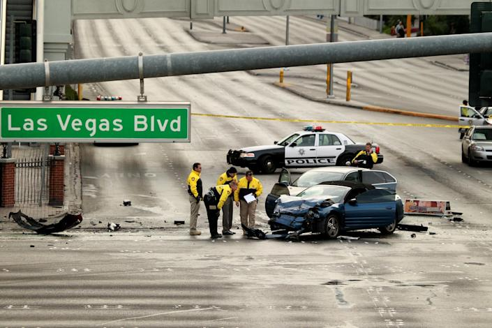 FILE - In this Feb. 21, 2013 file photo, law enforcement personal investigate the scene of a mulit-vehicle accident on Las Vegas Blvd and Flamingo Road Thursday, Feb. 21, 2013. Variously known as an adult playground and Disneyland for grown-ups, Las Vegas has worked to brand itself as a place where tourists can enjoy a sense of edginess with no real danger. But a series of high-profile and seemingly random incidents that have left visitors to the Strip dead or in the hospital is threatening Sin City's reputation as a padded room of a town where people can cut loose with no fear of consequences. (AP Photo/Las Vegas Review-Journal, Jeff Scheid) LOCAL TV OUT; LOCAL INTERNET OUT; LAS VEGAS SUN OUT