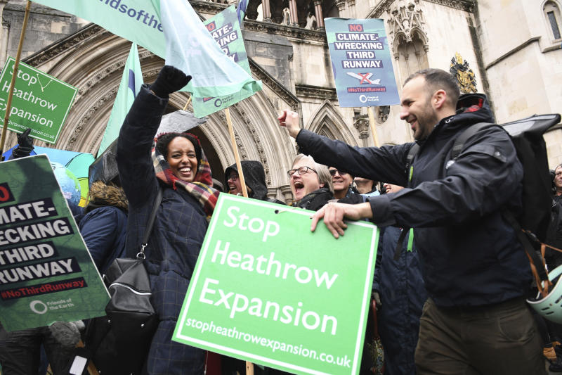 Campaigners cheer outside the Royal Courts of Justice in London, Thursday Feb. 27, 2020. Campaigners have won a court ruling to block the plans for a third runway at Heathrow Airport on environmental grounds. The case before Britain's Court of Appeal could stall the 14 billion-pound ($18 billion) plan to expand Heathrow Airport. (Stefan Rousseau/PA via AP)