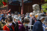 Visitors wearing face masks wait in line to enter a public park in Beijing, Saturday, May 1, 2021. Chinese tourists are expected to make a total of 18.3 million railway passenger trips on the first day of the country's five-day holiday for international labor day, according to an estimate by the state railway group, as tourists rush to travel domestically after the coronavirus has been brought under control in China.(AP Photo/Mark Schiefelbein)