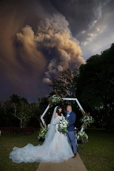 Social media image of a couple attending their wedding ceremony as Taal Volcano sends out a column of ash in the background in Alfonso, Cavite, Philippines
