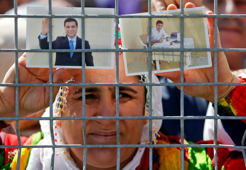 FILE PHOTO: A woman holds pictures of jailed former leader of Turkey's main pro-Kurdish Peoples' Democratic Party Selahattin Demirtas as people gather to celebrate Newroz, which marks the arrival of spring and the new year, in Istanbul