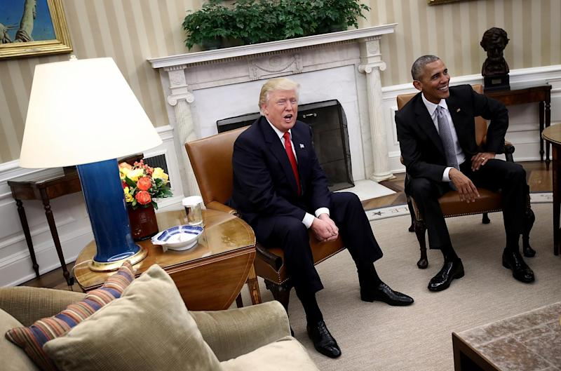 Donald Trump and Barack Obama enjoy a light-hearted exchange with journalists in the White House in December: Getty