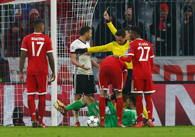 Soccer Football - Champions League Round of 16 First Leg - Bayern Munich vs Besiktas - Allianz Arena, Munich, Germany - February 20, 2018 Besiktas' Dusko Tosic is shown a yellow card by referee Ovidiu Hategan after a foul on Bayern Munich's Sven Ulreich REUTERS/Michaela Rehle