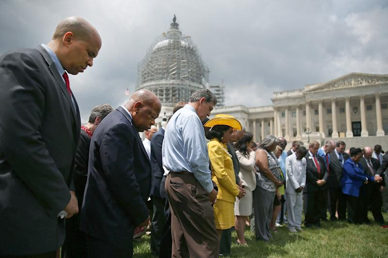Sen. Cory Booker and Rep. John Lewis take part in a 2015 prayer circle in front of the U.S. Capitol to honor those gunned down inside the historic Emanuel African Methodist Episcopal Church. (Mark Wilson/Getty Images)