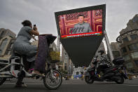 A woman on her electric-powered scooter films a large video screen outside a shopping mall showing Chinese President Xi Jinping speaking during an event to commemorate the 100th anniversary of China's Communist Party at Tiananmen Square in Beijing, Thursday, July 1, 2021.(AP Photo/Andy Wong)