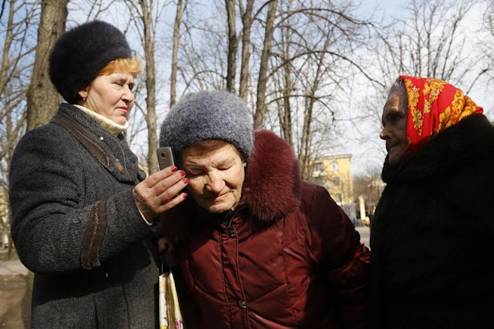 In this photo taken Tuesday, March 11, 2014, women listen to a statement given earlier in the day by Ukrainian President Viktor Yanukovich from Rostov-on-Don, Russia in Luhansk, eastern Ukraine. The pro-Moscow president fled office last month after prolonged street protests and bloodshed in Kiev, and was succeeded by a government made up of politicians friendlier to the United States and European Union. (AP Photo/Sergei Grits)