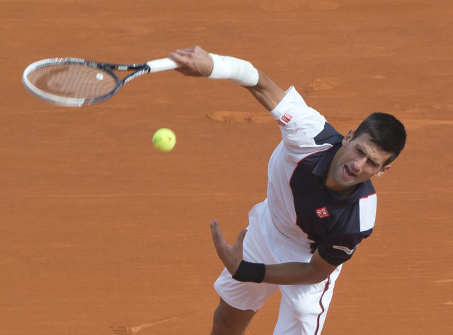Novak Djokovic of Serbia serves the ball to Roger Federer of Switzerland during their semifinal match of the Monte Carlo Tennis Masters tournament in Monaco, Saturday, April 19, 2014. Federer won 7-6 6-2. (AP Photo/Michel Euler)