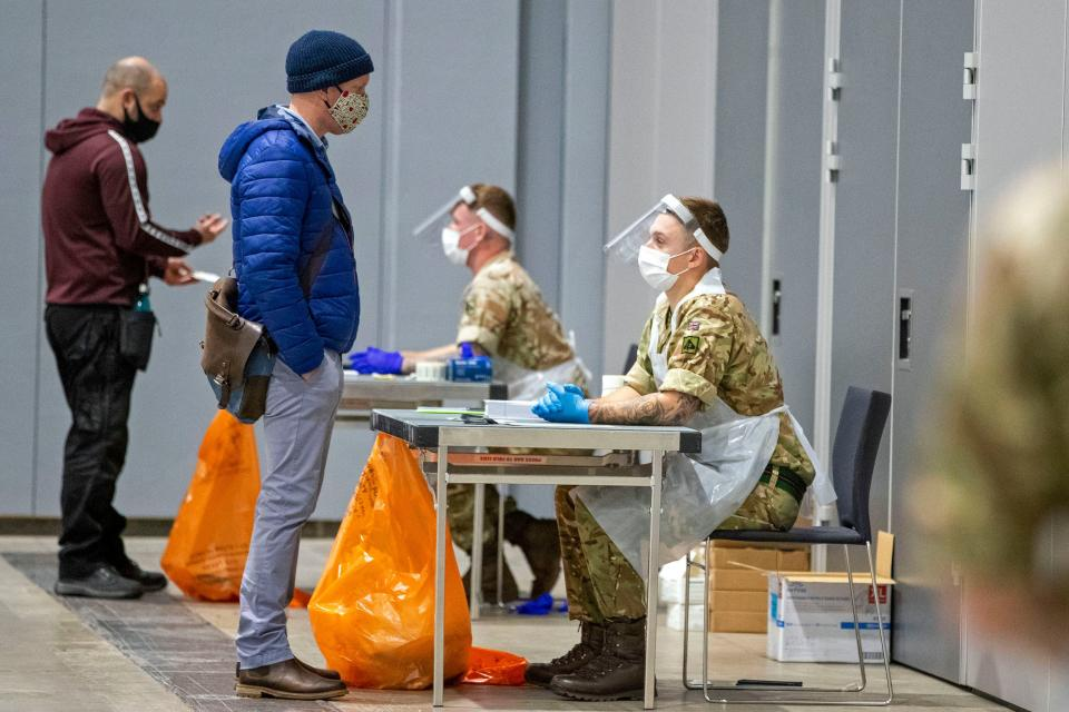 Members of the public are processed by soldiers wearing full PPE (personal protective equipment) at The Exhibition Centre in Liverpool, set up as a mass and rapid testing centre for the novel coronavirus COVID-19, on November 6, 2020. - To avoid extending the lockdown, Johnson is pinning his hopes on an ambitious new programme of Covid testing to detect and isolate infected people, starting with a city-wide trial launching in Liverpool today. (Photo by Peter Byrne / POOL / AFP) (Photo by PETER BYRNE/POOL/AFP via Getty Images)