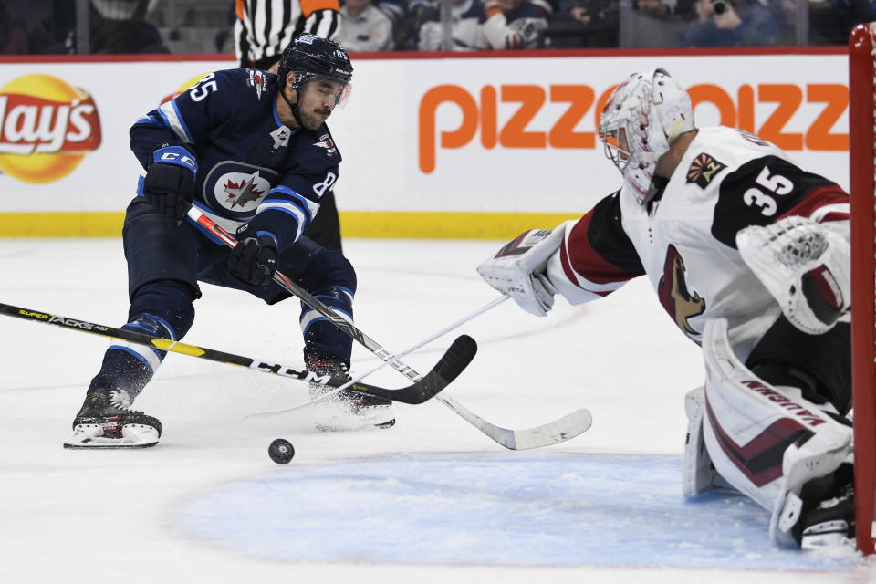 Arizona Coyotes goaltender Darcy Kuemper (35) makes a save on Winnipeg Jets' Mathieu Perreault (85) during the second period of an NHL hockey game Tuesday, Oct. 15, 2019, in Winnipeg, Manitoba. (Fred Greenslade/The Canadian Press via AP)