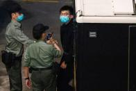 Pro-democracy activist Joshua Wong looks on upon arriving at Lai Chi Kok Reception Centre after he remained in custody over the national security law charge, in the early morning, in Hong Kong