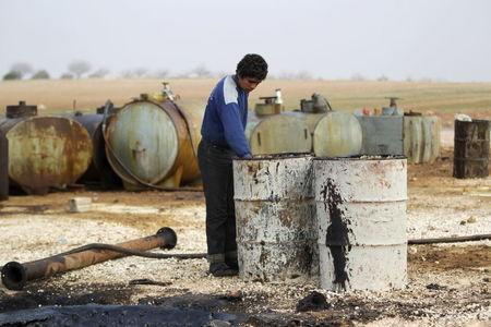 A youth works at a makeshift oil refinery site in Marchmarin town, southern countryside of Idlib, Syria