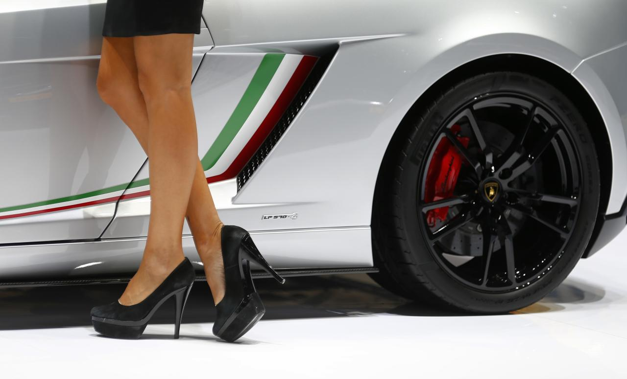 A model poses next to a Lamborghini Gallardo during a media preview day at the Frankfurt Motor Show (IAA) September 11, 2013. The world's biggest auto show is open to the public September 14 -22. REUTERS/Kai Pfaffenbach (GERMANY - Tags: TRANSPORT BUSINESS)