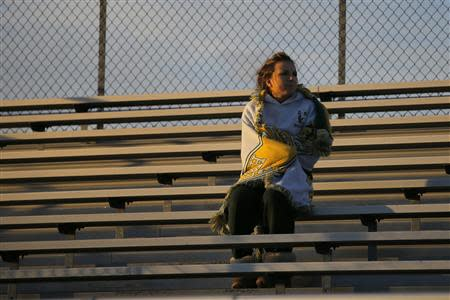 Fifteen year-old Sarah Steenhuysen watches her high school soccer teammates warmup before a game against Bishop Feehan in Attleboro, Massachusetts October 25, 2013. REUTERS/Brian Snyder