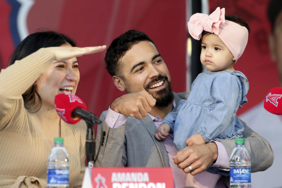 Los Angeles Angels Anthony Rendon, center, with his wife, Amanda Rendon, and their 17-month-old daughter, Emma look over at the audience during a baseball news conference in Anaheim, Calif., Saturday, Dec. 14, 2019. Rendon and the Angels agreed to a $245 million, seven-year contract earlier in the week. (AP Photo/Alex Gallardo)