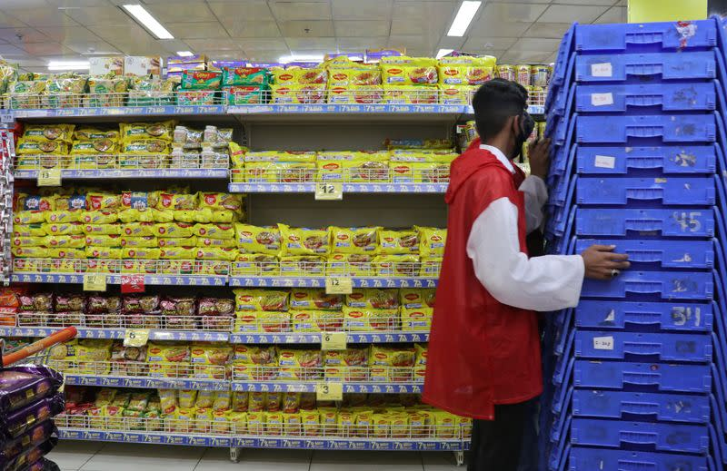 A worker pushes shopping baskets next to packets of Nestle's Maggi noodles and Reliance's Snac tac noodles inside a Reliance supermarket in Mumbai
