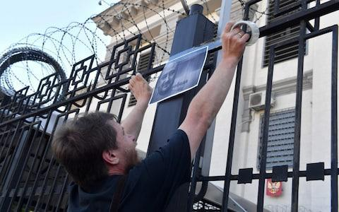 <span>An activists hangs portraits of journalist Arkadi Babchenko to the fence of Russian embassy in Kiev, on May 30, 2018, </span> <span>Credit: SERGEI SUPINSKY/AFP </span>