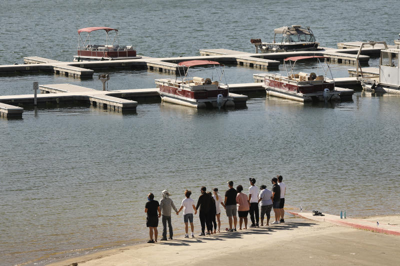 Cast members from Glee and friends of Naya Rivera's hold hands at Lake Piru