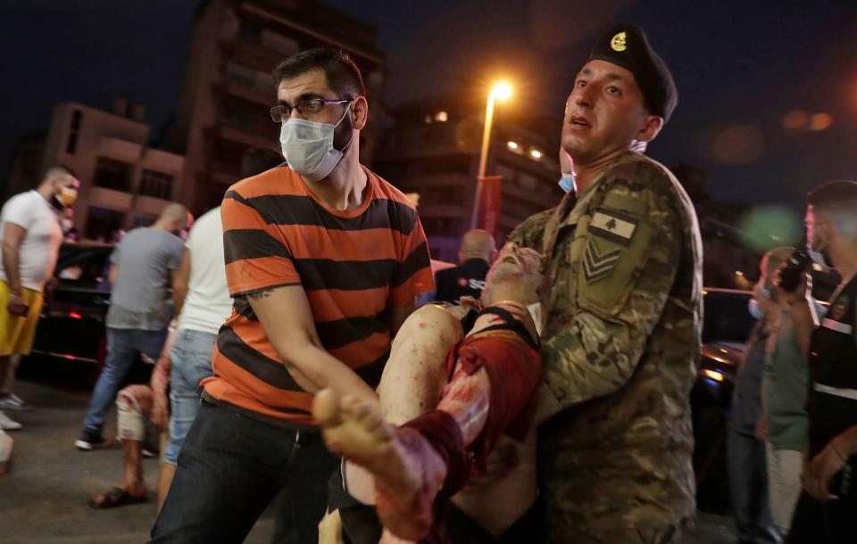 Un civil y un militar cargan con una persona herida que va a ser trasladada al hospital. (Photo by IBRAHIM AMRO/AFP via Getty Images)