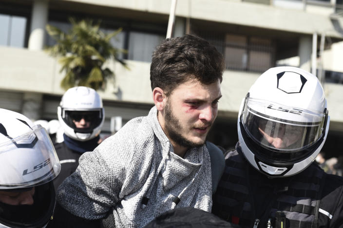 Police detain a protester at the University of Thessaloniki in northern Greece , on Monday, Feb. 22, 2021. Police clashed with protesters and detained more than 30 people in Greece's second-largest city Monday during a demonstration against a new campus security law. (AP Photo/Giannis Papanikos)