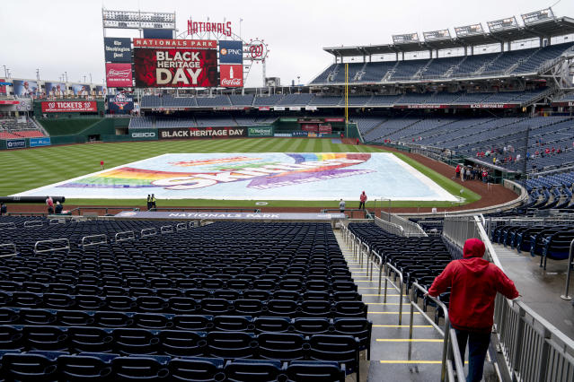 The infield is covered on a rainy Jackie Robinson Day before a baseball game between the Washington Nationals and the Colorado Rockies at Nationals Park on Sunday, April 15, 2018, in Washington. (AP Photo/Andrew Harnik)