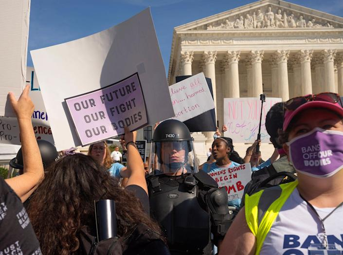 Protesters and counter-protestors meet outside of the Supreme Court at the Women's March and Rally for Abortion Justice in Washington, DC, on October 2, 2021.  Counter-protestors are behind the gates on the side of the Supreme Court, protected by a swat team and police officers.