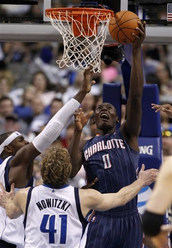 Charlotte Bobcats center Bismack Biyombo (0), of the Republic of the Congo, goes up for a shot as Dallas Mavericks' Brendan Haywood, left, and Dirk Nowitzki (41), of Germany, defend in the first half of an NBA basketball game on Thursday, March 15, 2012, in Dallas. (AP Photo/Tony Gutierrez)